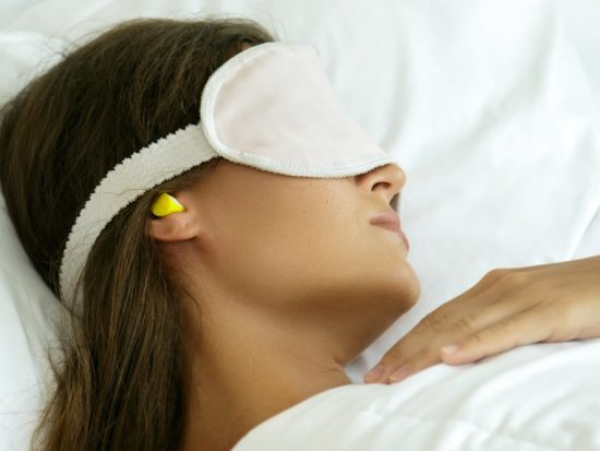 Woman sleeping on flight wearing an eye mask