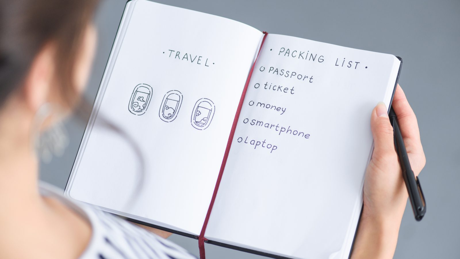 Single woman traveler writing down her packing list for travel
