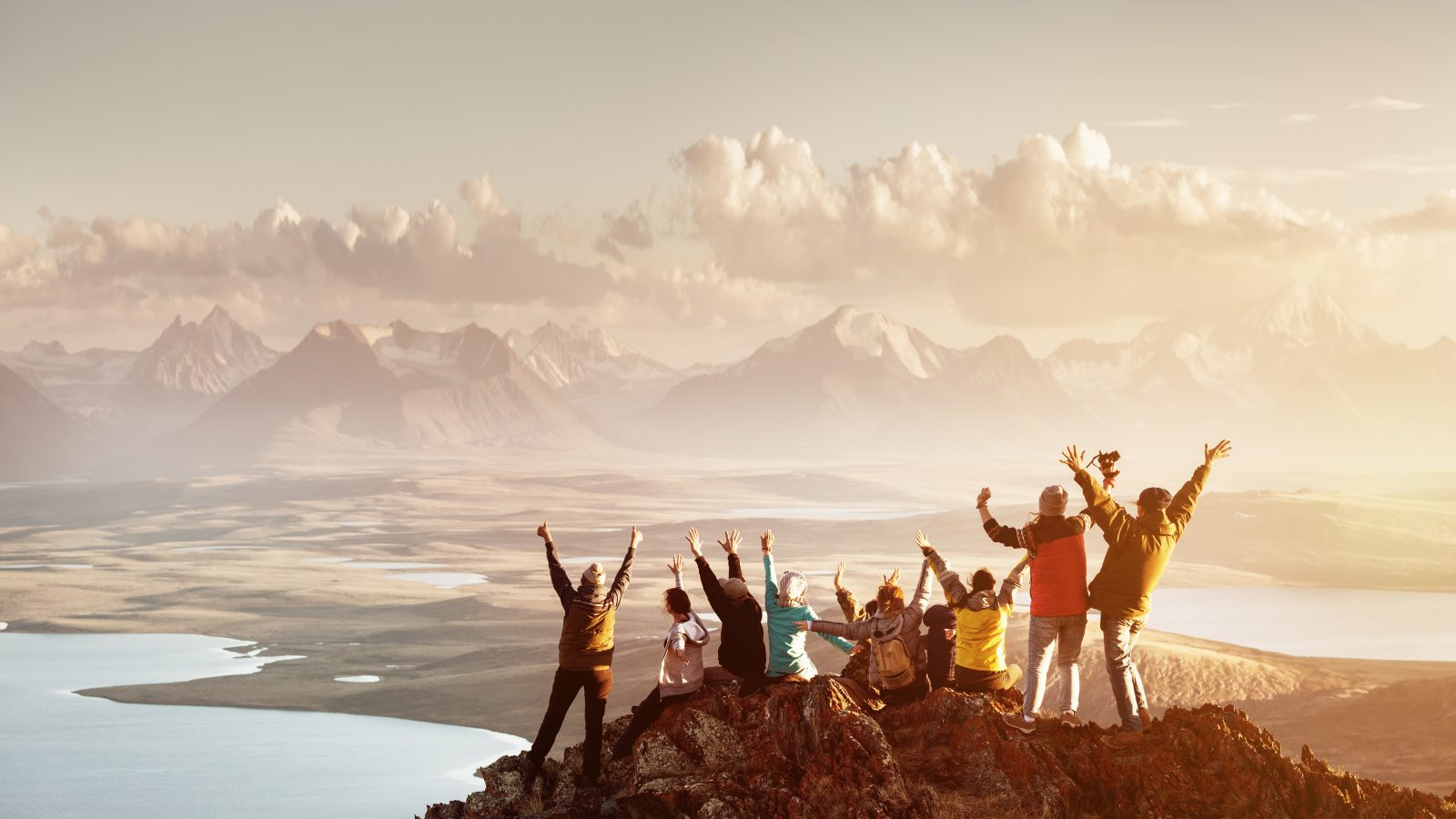 Big group of people success mountain top - group travel resources
