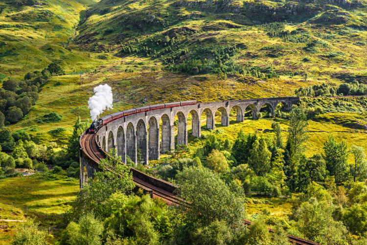 Glenfinnan Railway Viaduct in Scotland with the Jacobite steam train passing over - the perfect way to experience train travel in the UK
