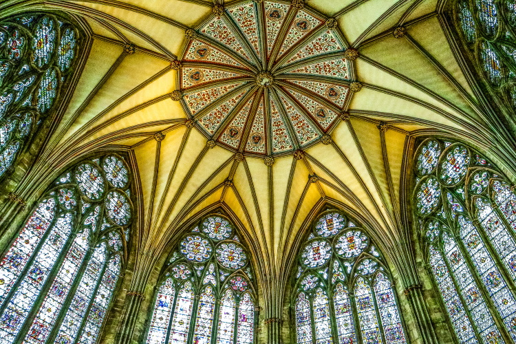 The intricate ceiling and medieval stained glass windows of the clositer at York Minster, York
