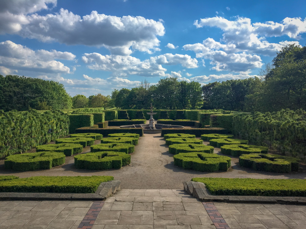 Gardens at Temple Newsam Leeds, with manicured box hedges under blue sky with fluffy white clouds