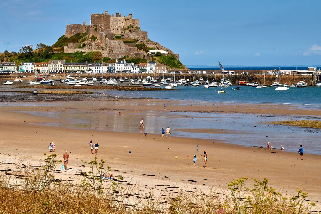Beach goers on Grouville Beach in Jersey, with Mont Orgueil Castle in the background