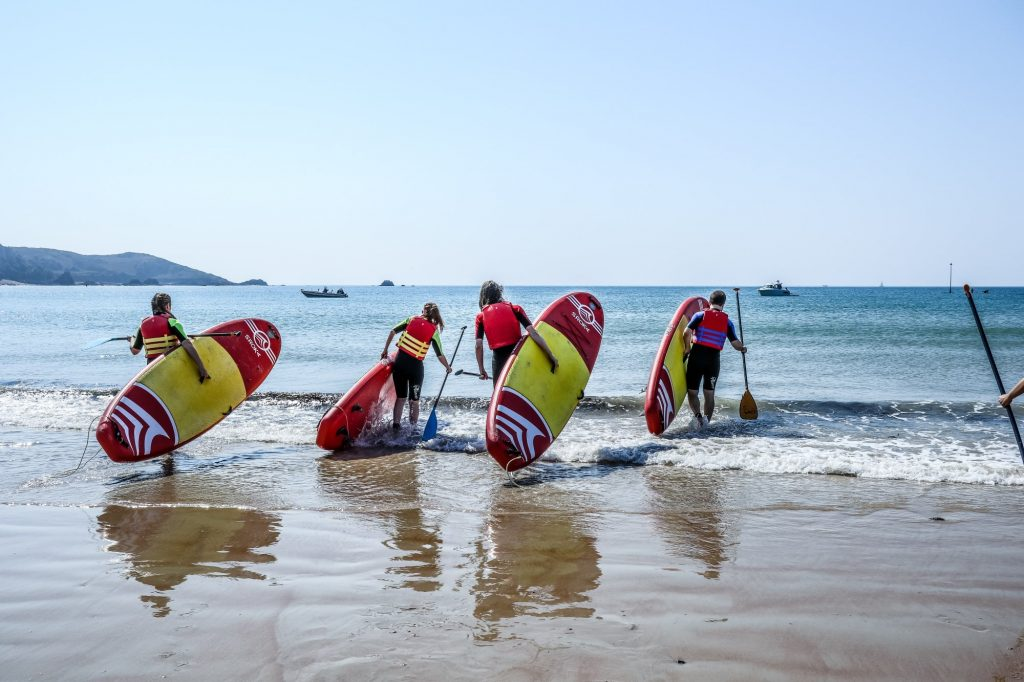 Paddle boarders carrying their boards through the surf at St Brelade's Bay, one of Jersey's best beaches